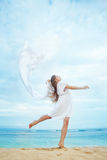 Woman jumping with cloth on a beach Royalty Free Stock Images