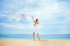 Woman jumping with cloth on a beach Stock Images