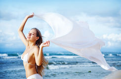 Woman jumping with cloth on a beach Stock Image