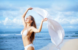 Woman jumping with cloth on a beach stock photo