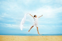 Woman jumping with cloth on a beach Royalty Free Stock Photos
