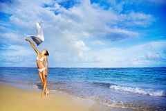 Woman jumping with cloth on a beach Royalty Free Stock Photo