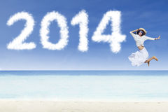 Woman jumping with clouds of 2014 Royalty Free Stock Images