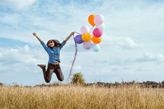 Woman jumping with colorful balloons in the meadow stock photos
