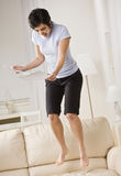 Woman Jumping on Couch Stock Image