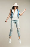 Woman jumping in denim waistcoat and hat Stock Photography