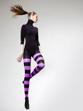 Woman jumping dressed in purple striped tights and black top - copy space Stock Photos
