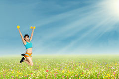 Woman jumping with dumbbells Stock Photos
