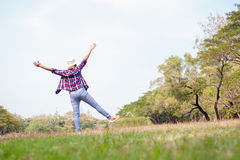 Woman jumping enjoying relax on green grass and flower field in Stock Photography