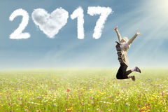 Woman jumping on flowers field with 2017. Image of attractive woman jumping on a flowers field with clouds shaped love and number 2017 in the clear sky Royalty Free Stock Image