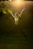 Woman jumping in forest at sunrise time Royalty Free Stock Image