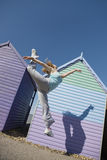 Woman Jumping In Front Of Beach Hut Stock Image