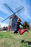 Woman jumping in front of the Eastham Windmill. The historic old fashioned mill sits in a Cape Cod Park in Massachusetts. Fisheye. Woman jumping in front of the royalty free stock images