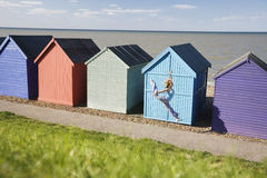 Woman Jumping In Front Of Huts At Beach Stock Image