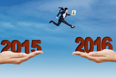 Woman jumping through the gap with numbers 2016 Stock Image