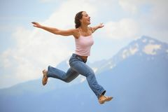 Woman is jumping with hands wide apart Royalty Free Stock Image