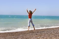 Woman jumping happily on the beach. Young woman jumping happily on the beach Royalty Free Stock Images