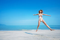 Woman jumping happily in swimsuit. Woman in swimsuit happy jumping and relaxing by the beach Royalty Free Stock Photos