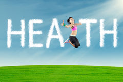 Woman jumping with health text at field Stock Image