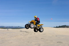 Woman jumping her ATV in the dunes Royalty Free Stock Photos