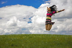 Woman Jumping for Joy. In the meadow stock photo