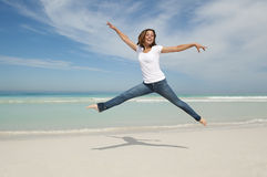 Woman jumping for joy at beach. Happy cheerful young sexy woman jumping full of joy at beach with arms up,  with ocean and blue sky as background and copy space Stock Images