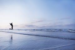 Woman jumping for joy on beach at sunrise Stock Photos