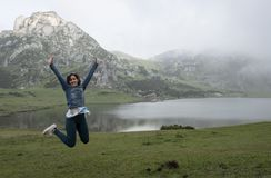 Woman jumping for joy in front of a lake in a mountainous landscape, in lakes of covadonga stock photography