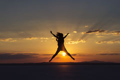 Woman jumping for joy and happines on sunset.  royalty free stock photo