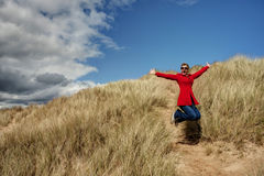 Woman jumping for joy. In the sandunes Royalty Free Stock Images