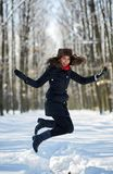 Woman jumping for joy in the snow. Young woman jumping for joy in the snow royalty free stock images