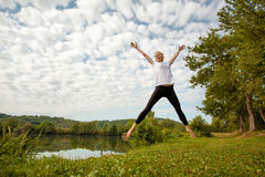 Woman jumping by the lake Royalty Free Stock Photography