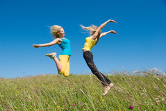 Woman jumping on meadow and blue sky Stock Photos