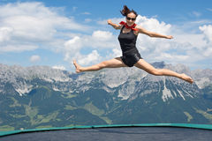 Woman jumping at mountain Royalty Free Stock Images