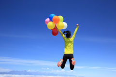 Woman jumping on mountain peak with colorful balloons Royalty Free Stock Photography