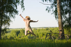Woman jumping at nature. 50 years old woman with bicycle jumping in  birch forest at summer Royalty Free Stock Image