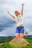 Woman jumping near chocolate hills in Philippines Stock Image