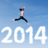 Woman jumping with new year 2014 of clouds. Excited asian woman is jumping with new year 2014 on the sky Royalty Free Stock Photos