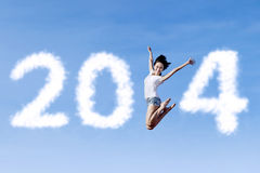 Woman jumping with new year 2014. Excited asian woman is jumping with new year 2014 on the clear sky Stock Image
