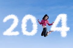 Woman jumping with new year 2014. Happy asian woman is jumping with new year 2014 on blue sky Royalty Free Stock Photos
