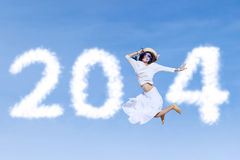 Woman jumping with new year 2014 on the sky. Happy young woman is jumping with new year 2014 on the sky Royalty Free Stock Photo