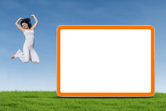 Woman jumping next to empty board Stock Photos