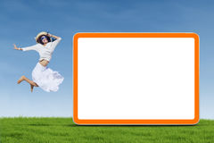 Woman jumping next to empty board Stock Images