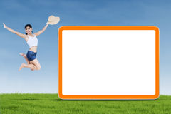 Woman jumping next to empty board Royalty Free Stock Photos