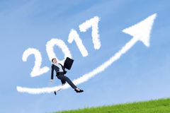 Woman jumping with number 2017 and arrow Stock Photo