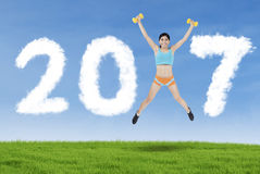 Woman jumping with number 2017 in the meadow Stock Images