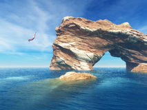 Woman jumping off cliff into the ocean. Stock Images