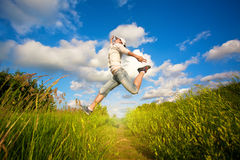 Woman jumping over the blue sky Stock Photo
