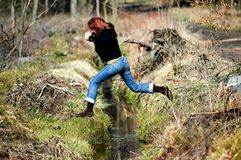 Woman jumping over creek Royalty Free Stock Photography