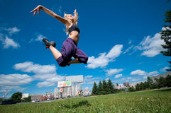 Woman jumping over green city street Royalty Free Stock Photo
